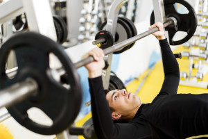 Closeup of young handsome man doing exercises on a bench press