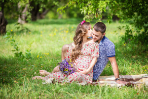 Happy young couple expecting baby, pregnant woman kissing her husband, sitting on green grass