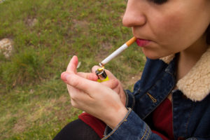 Smoking girl in the field on a cloudy day. She is lighting the cigar lighter.